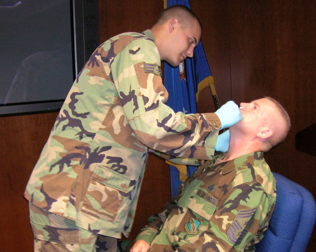 Senior Airman Jeremy Means, emergency medical technician, gives Chief Master Sgt. Layton Clark, 4th Fighter Wing command chief master sergeant, a FluMist vaccination Oct. 6.  (U.S. Air Force photo by Robin DeMark)