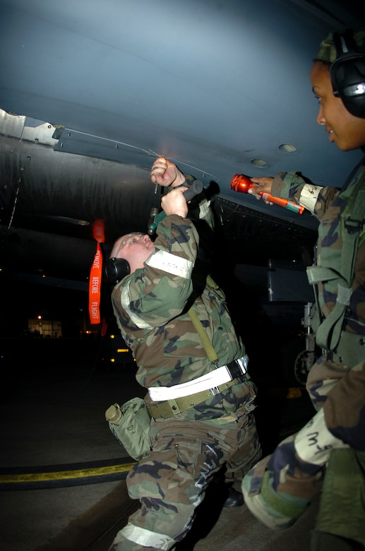 Staff Sergeant Duncan Tripp and Senior Airman Camile Davis, 4th Equipment Maintenance Squadron, perform routine maintenance on a F-15E Strike Eagle during a Phase II Exercise October 4, 2006. The exercise is one of many in preparation for an   Operational Readiness Inspection in January of 2007 that will test the base's war readiness. (U.S. Air Force photo by A1C Greg Biondo)