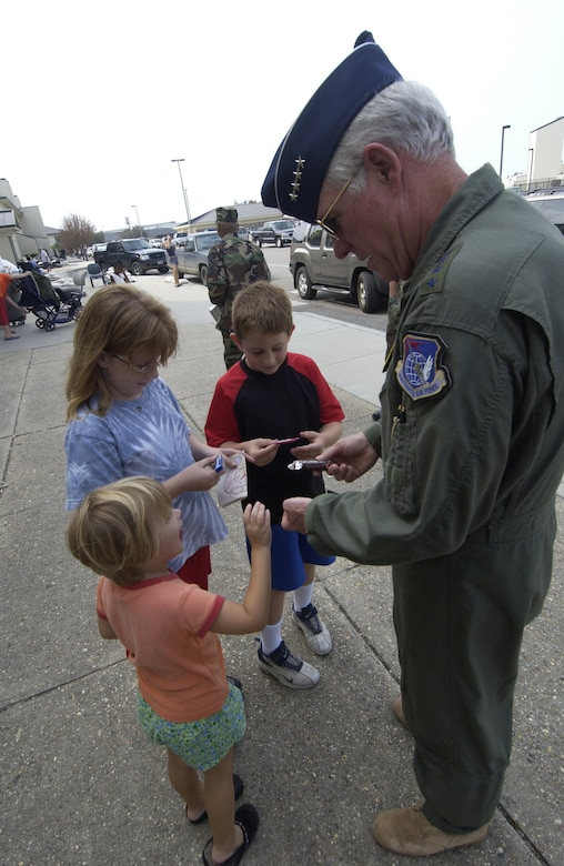 Gen. William R. Looney III, Air Education and Training Command commander, gets a smile from some children at Keesler Air Force Base as he passes out candy during a trip to the base Thursday. General Looney surveyed the damaged caused by Hurricane Katrina and learned first-hand how the command can support. (Photo by TSgt Jennifer C. Wallis, 1st Combat Camera Squadron)