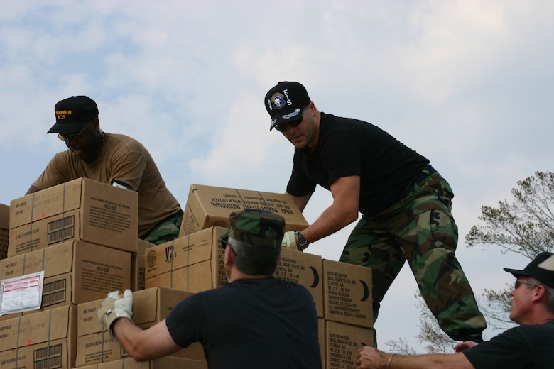 KEESLER AIR FORCE BASE, Miss. (AETCNS) -- Atop a flatbed truck (from left), Senior Master Sgt. Darrell King, 83rd Communications Squadron, Langley AFB, Va., and Col. Paul Farkas, commander of Keesler's 85th Engineering and Installation Squadron, unload Meals Ready to Eat at a Biloxi, Miss., humanitarian aid station for Hurricane Katrina victims during a relief mission Sept. 3. Despite being impacted by the devastating storm themselves, dozens of Keesler's Air Force, Navy and Marine Corps members, including deployed troops, are welcoming the opportunity to show their support for their Mississippi Gulf Coast community neighbors. (U.S. Air Force photo by Master Sgt. Dan Oberly)