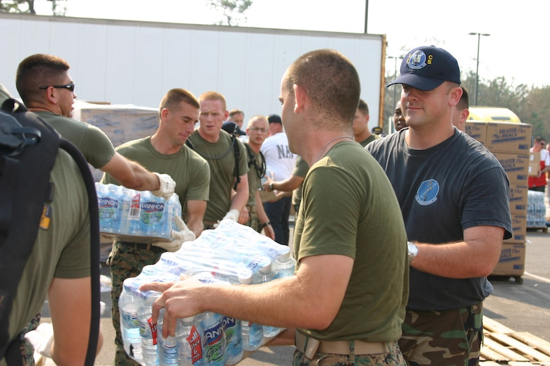 KEESLER AIR FORCE BASE, Miss. (AETCNS) -- Capt. Robert Frees (right), 83rd Communications Squadron HAMMER ACE chief, assists fellow volunteers from the Marine Corps detachment here as they off load bottled water to a local supply distribution center during a humanitarian mission Sept. 3. Keesler volunteers delivered nearly 12,000 Meals Ready to Eat and more than 11,000 bottles of water to hurricane victims. (U.S. Air Force photo by Master Sgt. Dan Oberly)