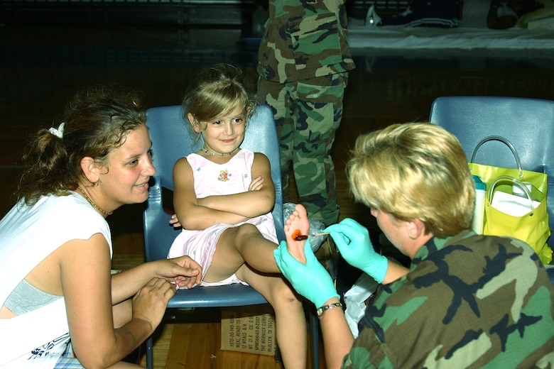 KEESLER AIR FORCE BASE, Miss. (AETCNS) -- Capt. Tracey Gosser, 81st Medical Group Neonatal Intensive Care Unit officer in charge, treats 5-year-old Alexes Wisniewski's foot after removing some glass, while Alexes' mother, Patter, looks on. The captain is part of a medical team from Keesler Air Force Base, Miss., that travels to local shelters to provide medical care. (U.S. Air Force photo by Master Sgt. Dan Oberly)