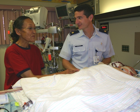 Maj. (Dr.) Christopher Coppola and Dora Hill discuss her son's status in the Wilford Hall Pediatric Intensive Care Unit. Dr. Coppola, a pediatric surgeon with the 859th Surgical Operations Squadron, was part of the team that flew to Anchorage, Alaska, Aug. 14, in an attempt to save Michael's life. (Photo by Sue Campbell)