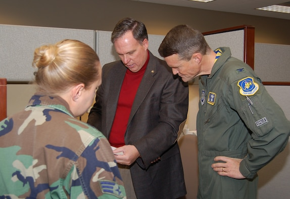 Senior Airman Amy Daub, from the 460th Medical Group, watches and listens as Scott Rogers, from the 460th Contracting Squadron, briefs 460th Space Wing Commander Col. David Ziegler about his ongoing projects. Airman Daub participated in the shadow program, in which a junior enlisted member tags along with Colonel Ziegler for two days, Oct. 17 and 18.