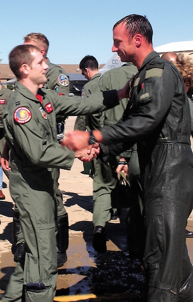 "CANNON AIR FORCE BASE, N.M. -- Capt. Ryan ""Rock"" Wartman, left, and Capt. Steven ""Amp"" Frodsham, 522nd Fighter Squadron pilots, talk Oct. 13 after Captain Frodsham's fini flight – his last at Cannon. Captain Frodsham is the Air Combat Command Instructor Pilot of the Year for 2005 and is heading to Langley Air Force Base, Va. (U.S. Air Force photo/ Airman 1st Class Tiffany Curbeam)"