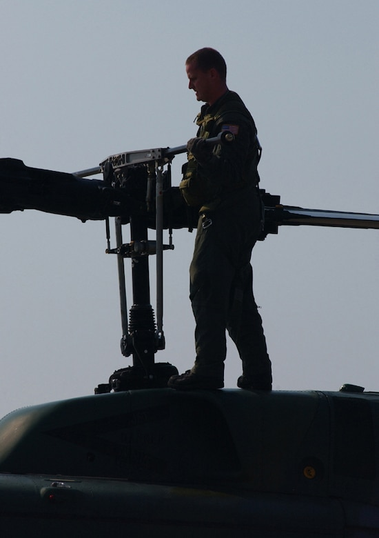 Staff Sgt. Adam Lasher, a former flight engineer for the 76th Helicopter Squadron, does a preflight check to ensure the helicopter is air worthy.