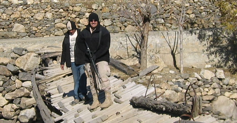 Staff Sgt. Chad Louis and an interpreter cross a broken bridge at the site of a future project to replace bridges in Rakh, Afgahnistan. Sergeant Louis and the interpreter were members of a 25 person provincial reconstruction team stationed in Afgahnistan.