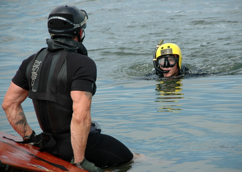 Tech. Sgt. Will Wilis, Pararescue Instructor 342nd Training Squadron (front), reaches Rigging Alternate Method Zodiac package first as Staff Sgt. Josh Webster and other air-dropped PJ trainees swim to unpack it. (U.S. Air Force photo by Senior Airman Jonathan Simmons) (Released)