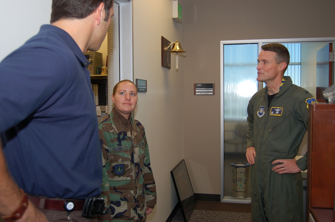 Senior Airman Amy Daub, from the 460th Medical Group, talks with a member of the 460th Contracting Squadron with 460th Space Wing Commander Col. David Ziegler. Airman Daub shadowed Colonel Ziegler for two days as part of the commander shadow program. (U.S. Air Force photo by Senior Airman Jacque Lickteig)