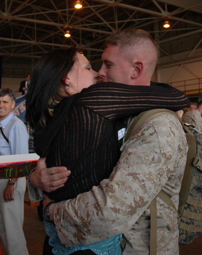 Lance Cpl. Nick Jenkins, Alpha Battery, 1st Battalion, 14th Marines, 4th Marine Division member, kisses his wife, Mrs. Amee Jenkins, after being away from her for 10 months. He and about 130 members from his unit spent about seven of those months in Iraq supporting Operation Iraqi Freedom. (U.S. Air Force photo by Senior Airman Jacque Lickteig)