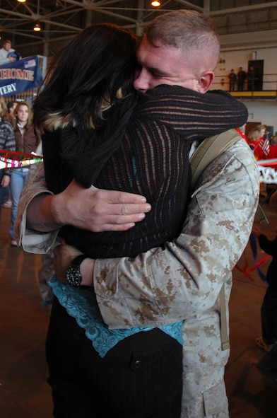 Lance Cpl. Nick Jenkins greets his wife, Mrs. Amee Jenkins, after returning home from Operation Iraqi Freedom with about 130 fellow Battery A, 1st Battalion 14th Marine Regiment, 4th Marine Division Marines and Sailors Oct. 20. (U.S. Air Force photo by Senior Airman Jacque Lickteig)