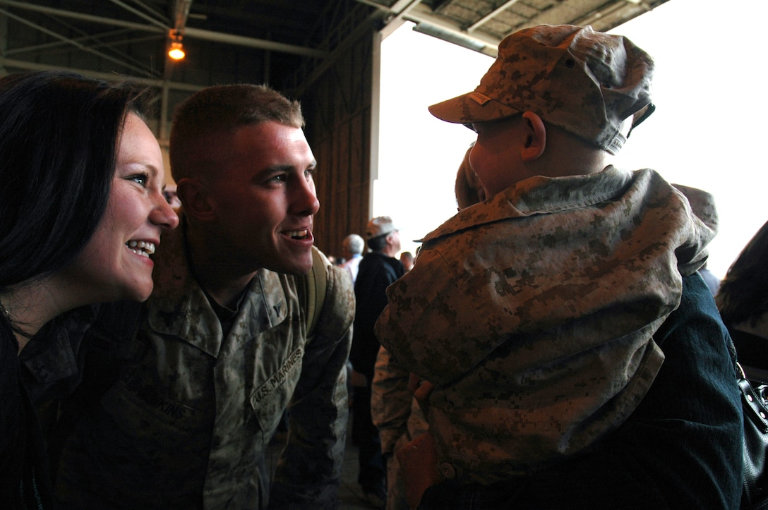 Lance Cpl. Nick Jenkins greets his year-old son, Dylan, and his wife, Mrs. Amee Jenkins, after returning home from Operation Iraqi Freedom with about 130 fellow Battery A, 1st Battalion 14th Marine Regiment, 4th Marine Division Marines and Sailors Oct. 20. The Marines and Sailors served as a provisional military police company. (U.S. Air Force photo by Senior Airman Jacque Lickteig)