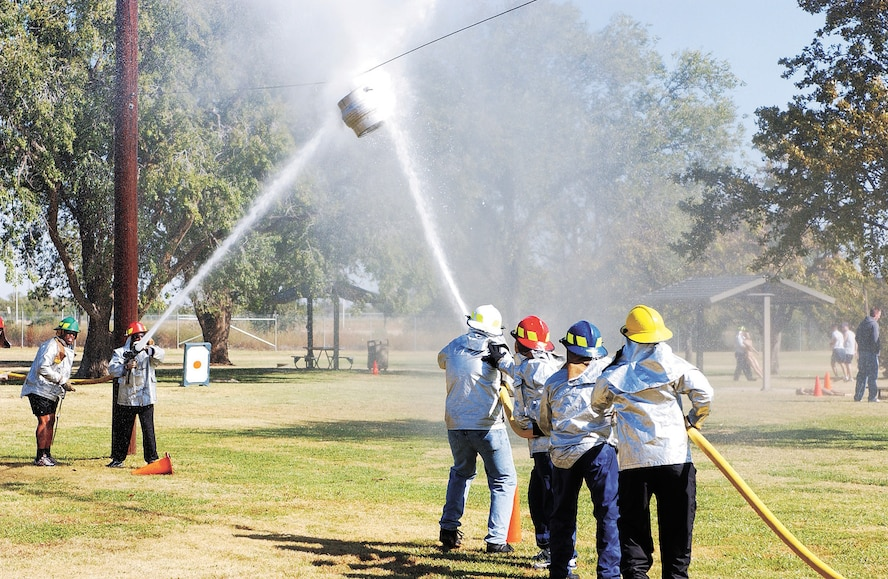 CANNON AIR FORCE BASE, N.M. -- The 27th Ccommunications Squadron and the 27th Civil Engineer Squadron test their spraying accuracy by pushing a keg across a wire in the Waterball competition at the annual Fire Muster Oct. 13. (U.S. Air Force photo/ Airman 1st Class Randi Rickards)
