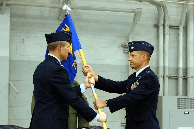 Col. Mark Alsid, 16th Operations Group commander, passes Lt. Col. Tom Markland, 73rd Special Operations Squadron commander, the guidon during the stand-up ceremony Tuesday in Commando Hangar. (U.S. Air Force Photograph by Airman 1st Class Stephanie Sinclair)