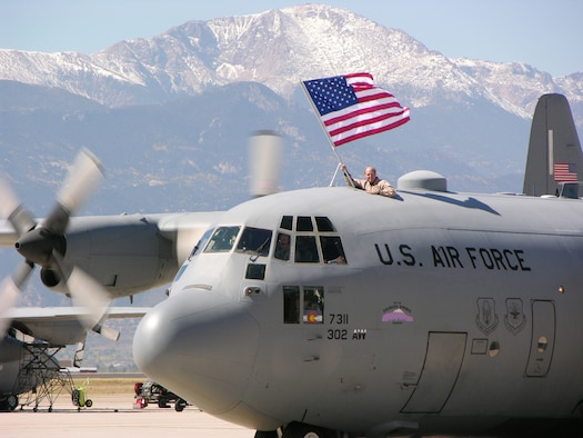 PETERSON AIR FORCE BASE, Colo. (AFRC) -- Maj. Stephen Stelly, 731st Airlift Squadron flight commander, proudly displays the American flag as a 302nd Airlift Wing C-130 taxis past Pikes Peak during a recent homecoming. On Oct. 4, wing members ended 14 months of deployments in support of U.S. Central Command operations in Southwest Asia. (U.S. Air Force photo by Master Sgt. Mark Clark)