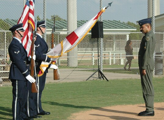 PANAMA CITY BEACH, Fla. --  Col. Scott Davis, 325th Fighter Wing vice commander, salutes the flag as the colors are presented during the opening cermonies of a military world championship softball tournament in August at Frank Brown Park here. (U.S. Air Force photo by Chrissy Cuttita)