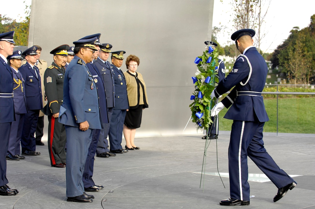 An Airman from the U.S. Air Force Honor Guard presents the wreath at the foreign dignitary arrival and wreath laying ceremony at the Air Force Memorial in Arlington, Va., on Oct. 24.  Air Force Chief of Staff Gen. T. Michael Moseley hosted the ceremony for nine Pacific air chiefs visiting Washington. Lt. Gen. Soeung Samnang, Cambodian Royal Air Force commander, represented the Pacific Air Chiefs  when he assisted Gen. Moseley during the ceremony. (U.S. Air Force photo/Senior Airman Desiree Andrejcik)