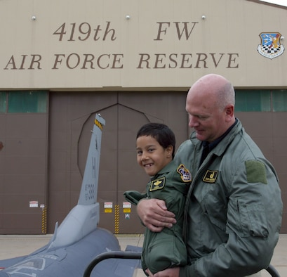 Gabe Adams, who was born with no arms or legs, is carried by his father, Ron Adams, as they prepare to climb into the backseat of an F-16D at the 419th Fighter Wing here Oct. 19.  (U.S. Air Force Photo/Tech. Sgt. Brian Pusey)