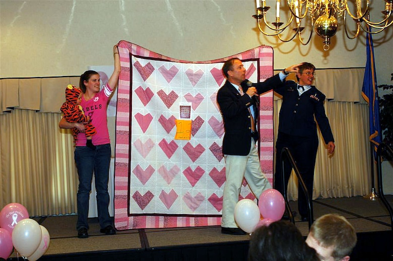 "Bill Large, from the 5th Medical Support Squadron, auctions off a quilt called ""Hearts for a Cure"" during the quilt auction for the National Breast Cancer Awareness Month event at Minot Air Force Base, N.D., Oct. 24, while the makers of the quilt -- Rebecca Ament and Lt. Col. Anne Heinly, 5th Medical Operations Squadron commander -- hold it up. All proceeds from the auction, which raised almost $4,000, were donated to breast cancer research through the Combined Federal Campaign. The event, themed ""Voices of Breast Cancer, Inspiring Hope, Supporting a Cure, included a health fair and the personal testimony of several breast cancer survivors from the base community. Photo By: Airman First Class Cassandra Butler"