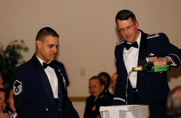 Col. Benjamin Huff, 30th Mission Support Group commander, and Master Sgt. David Matos, 30th Logistics Readiness Squadron, add apple cider to the grog bowl at the 30th Space Wing Dining Out here Oct. 20.