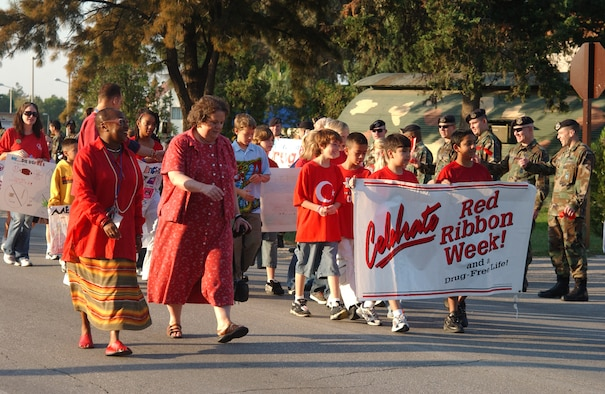Luciille Sutherland, far left, Incirlik American School assistant principal, and Sandra DiQuinzio, middle, IAS principal, lead IAS elementary school students down the road during the Red Ribbon Week parade against drugs, Oct. 26. (U.S. Air Force photo by Airman Kelly LeGuillon)