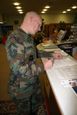 Senior Master Sgt. Todd Weidensaul, 39th Security Forces Squadron superintendent of plans and programs flight, fills out a form for use of the marquee at the community center Oct. 26. (U.S. Air Force photo by Staff Sgt. Oshawn Jefferson)