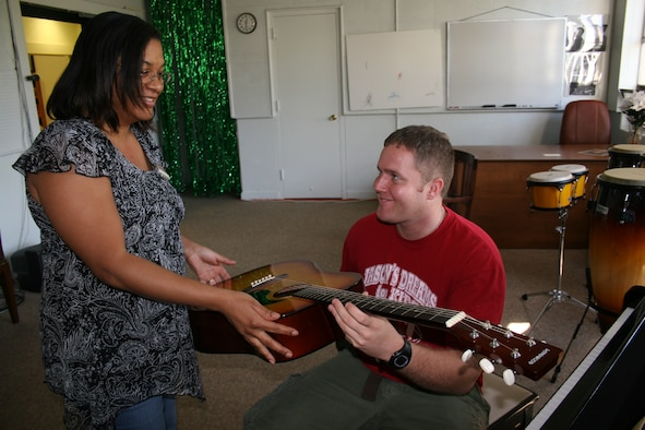 Selina Moorer. 39th Services Squadron community center assistant director, assists Senior Airman Danel Bevins. a New Jersey Air National Guard 108th Air Refueling Wing intelligence Airman, with an acoustic guitar at the community center Oct. 26. (U.S. Air Force photo by Staff Sgt. Oshawn Jefferson)