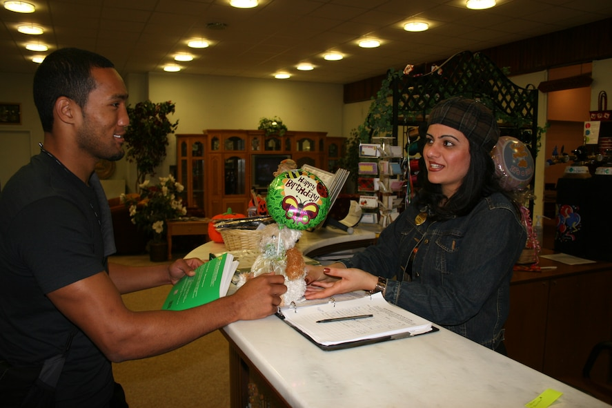 "Seckin Atims, 39th Services Squadron community center recreation specialist, assists Joseph Lipscomb, a 21-year-old dependent, with purchashing a birthday gift at the ""Just Because"" Ballon and Gift Shop inside the community center Oct. 26. (U.S. Air Force photo by Staff Sgt. Oshawn Jefferson)"
