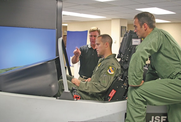 (Right) Capt. Matthew Phillips, a 335th Fighter Squadron pilot, looks on as Mike Barton, Lockheed Martin Pilot Vehicle Interface expert, gives a cockpit overview of the F-35 Lightening II simulator to 1st Lt. Christopher Beery, a 335th Fighter Squadron weapons system officer.  Members of the 333rd, 334th, 335th and 336th fighter squadrons had an opportunity to get an up close view of what the F-35 has to offer in the way of the latest fighter technology.  (U.S. Air Force photo by Staff Sgt. Les Waters)
