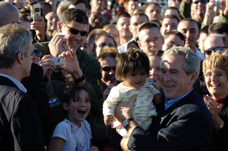 President George W. Bush holds a baby while greeting people after giving a motivational speech to the troops at Charleston Air Force Base, S.C., on Oct. 28, 2006. President Bush came to South Carolina to thank the Airmen at Charleston AFB for their contributions to the Global War on Terrorism. (U.S. Air Force photo by Senior Airman Desiree N. Palacios)(Released)