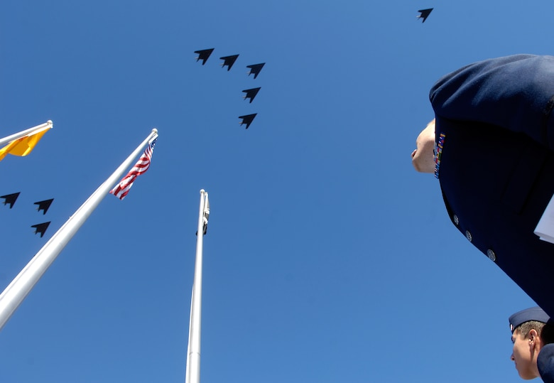 Capt. Heath Armstrong (front) and 2nd Lt. Scott Panzer watch as a formation of F-117 Nighthawks pass overhead. The formation was part of the Nighthawk's 25th anniversary and 250,000 flying-hour celebration at Holloman Air Force Base, N.M.  The formation consisted of 25 planes staggered into five separate groups. Captain Armstrong and Lieutenant Panzer are part of the 49th Operations Support Squadron. 