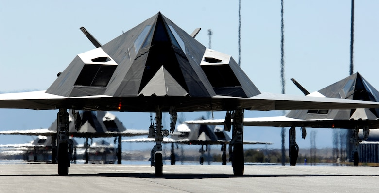 Twenty-five F-117 Nighthawks line up before takeoff from Holloman Air Force Base, N.M. The planes were part of a formation celebrating the Nighthawk's 25th anniversary and 250,000 flying hour. The 25 aircraft were separated into five groups and flew over the base to end the celebration ceremony. (U.S. Air Force photo/Senior Airman Brian Ferguson)
