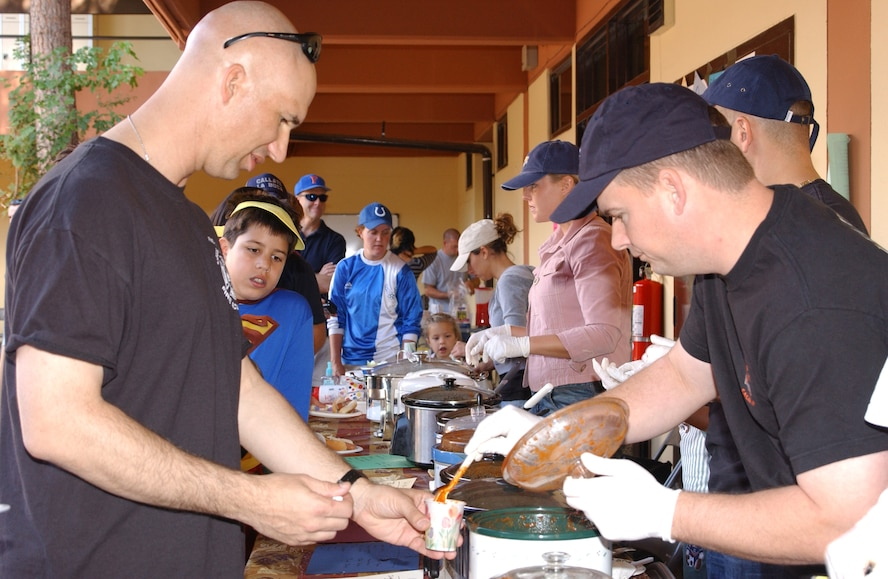 Tech. Sgt. Mike Gregory, right, gives Lt. Col. Scott Warner, a sample of his chili during the chili-cook off at the fall carnival Oct. 28. (U.S. Air Force photo by Airman 1st Class Tiffany Colburn)