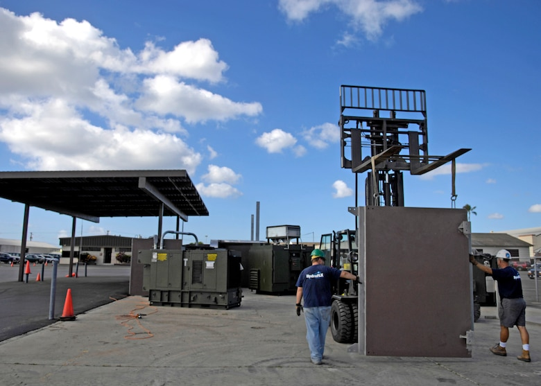 Members of HydraFLX Systems LLC move a containment wall during the building phase for the HydraFLX System at Hickam Air Force Base, Hawaii Oct. 27, 2006. The HydraFLX System is being tested by the Air Force as an alternate energy source. It will generate ultra-pure H2 (hydrogen) from water in a flexible pressure management process for fueling buses, tow-tractors, vans, sedans and ground support equipment. The system can also be deployed anywhere and operate in hostile theaters without infrastructure or pipelines. (U.S. Air Force photo/Tech. Sgt. Shane A. Cuomo)