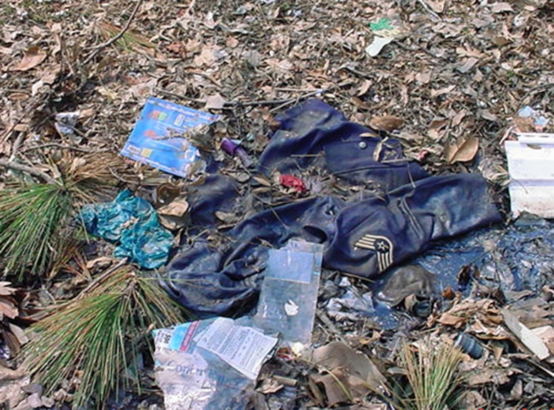 The enlisted uniforms of 1st Lt. Dawn Clifton lie in mud and trash in front of the Cliftons' home in Ocean Springs, Miss., after Hurricane Katrina. Lieutenant Clifton, who is prior enlisted, was stationed at Keesler Air Force Base, Miss., when the hurricane devastated the Gulf Coast in August 2005. (U.S. Air Force photo)