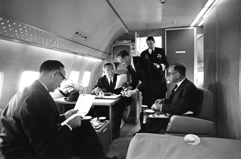 President Lyndon B. Johnson in the presidential bedroom aboard Air Force One (SAM 26000). From left to right are Sen. Mike Mansfield; President Johnson; Chief Master Sgt. Paul Glynn, serving president; U.S. Navy Aide Capt. Beach; and Sen. Fulbright. (U.S. Air Force photo)
