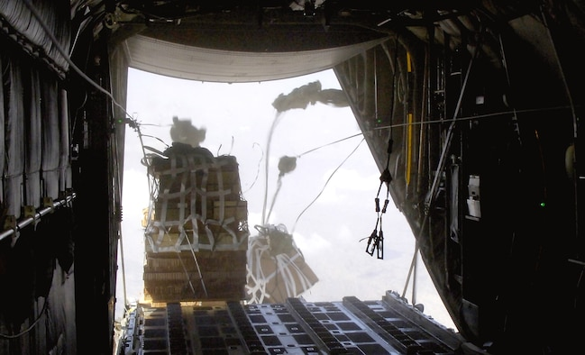 Joint Precision Air Drop System bundles fall out of the back of a C-130 Hercules Aug. 25. The drop was made from almost 10,000 feet above sea level and was calculated using up-to-the-minute wind data relayed from two small dropsondes deployed 20 minutes earlier. The dropsondes calculate wind speed and relay the information back to the aircraft, helping to calculate the correct drop point. (U.S. Air Force photo/Senior Airman Brian Ferguson)