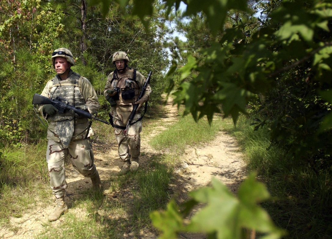 Capt. Michael Schroeder (front) and Tech. Sgt. Gene Lappe search for a land navigation point and improvised explosive devices Aug. 30 using techniques learned at Camp Shelby, Miss.  Camp Shelby is one of several Army installations providing training to military personnel preparing to deploy to Southwest Asia.  (U.S. Air Force photo/Tech. Sgt. Cecilio Ricardo Jr.)