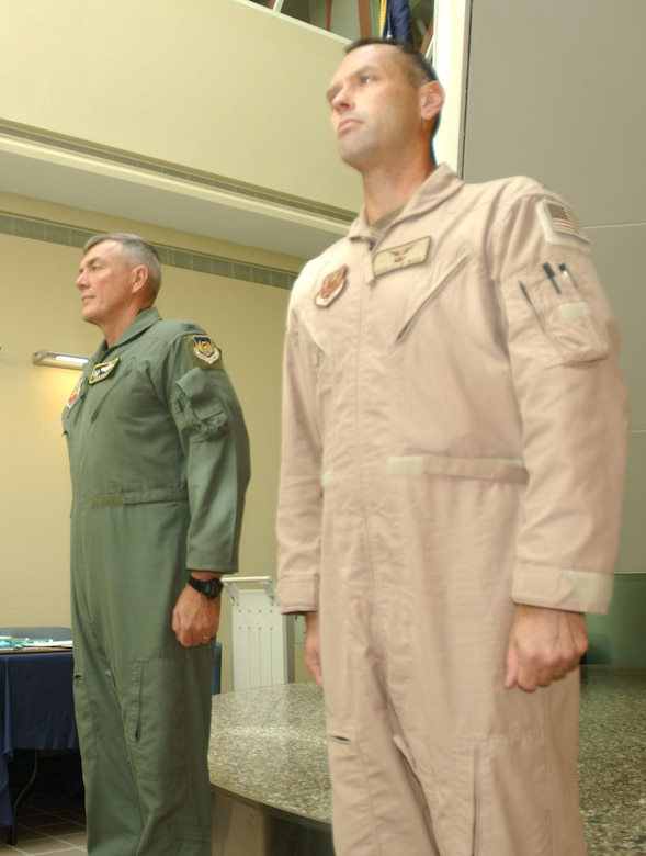 MINOT AIR FORCE BASE, N.D. -- Maj. Douglas Webb (far right), 5th  Medical Operations Squadron, stands at attention next to Col. Eldon Woodie, 5th Bomb Wing commander, before being presented the Bronze Star award during a ceremony at the 5th Medical Group building, Aug. 30. (U.S. Air Force photo by Airman Sharida Bishop)