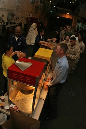 """ABOARD USS PELELIU (LHA 5) (Oct. 29, 2008) -- Sailors with the USS Peleliu (LHA 5), Marines with the 15th Marine Expeditionary Unit and """"Tigers"""" line up for popcorn during a Cinema at Sea in the hangar bay aboard USS Peleliu (LHA 5).::r::::n::   Operation Tiger Cruise is a program which brings civilian friends and family of deployed Marines and Sailors for the final leg of a deployment from Pearl Harbor, Hawaii to San Diego, Calif. aboard U.S. Navy vessels.::r::::n::   During Tiger Cruise, Tigers see the day-to-day operations their service members experience during deployment, including eating in the mess decks and sleeping in troop berthing. ::r::::n::    The Camp Pendleton, Calif. based 15th MEU is comprised of approximately 2,200 Marines and Sailors and is a forward deployed force of readiness capable of conducting numerous operations, such as Non-Combatant Evacuation Operations, Humanitarian Assistance Operations and a wide range of amphibious missions. ::r::::n::   The 15th MEU is currently on the final leg of deployment. (Official USMC photo by Cpl. Timothy T. Parish) (Released)::r::::n::::r::::n::"""