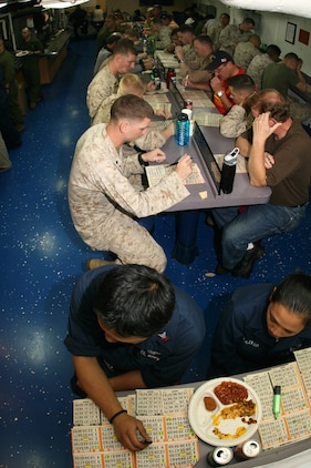 """ABOARD USS PELELIU (LHA 5) (Oct. 30, 2008) -- Sailors with the USS Peleliu (LHA 5), Marines with the 15th Marine Expeditionary Unit and """"Tigers"""" play bingo in the mess decks aboard USS Peleliu (LHA 5).::r::::n::   Operation Tiger Cruise is a program which brings civilian friends and family of deployed Marines and Sailors for the final leg of a deployment from Pearl Harbor, Hawaii to San Diego, Calif. aboard U.S. Navy vessels.::r::::n::   During Tiger Cruise, Tigers see the day-to-day operations their service members experience during deployment, including eating in the mess decks and sleeping in troop berthing. ::r::::n::    The Camp Pendleton, Calif. based 15th MEU is comprised of approximately 2,200 Marines and Sailors and is a forward deployed force of readiness capable of conducting numerous operations, such as Non-Combatant Evacuation Operations, Humanitarian Assistance Operations and a wide range of amphibious missions. ::r::::n::   The 15th MEU is currently on the final leg of deployment. (Official USMC photo by Cpl. Timothy T. Parish) (Released)::r::::n::"""