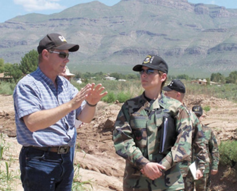 Otero County Public Works Director Bill Parker, left, talks with Lt. Col. Andra Clapsaddle, commander 49th Civil Engineer Squadron, as Airmen and county personnel begin clearing a section of land along the lower Alamo Canyon drainage channel.
