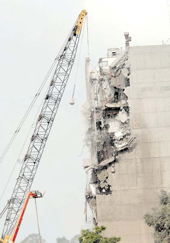Large chunks of concrete fall off as the wrecking ball takes another swing at Building 105, the former Space and Missile Systems Center's main building in Area A. Other structures have been systematically demolished by a private crew to make way for a residential neighborhood. The process is in accordance with the Systems Acquisition Management Support Complex project.