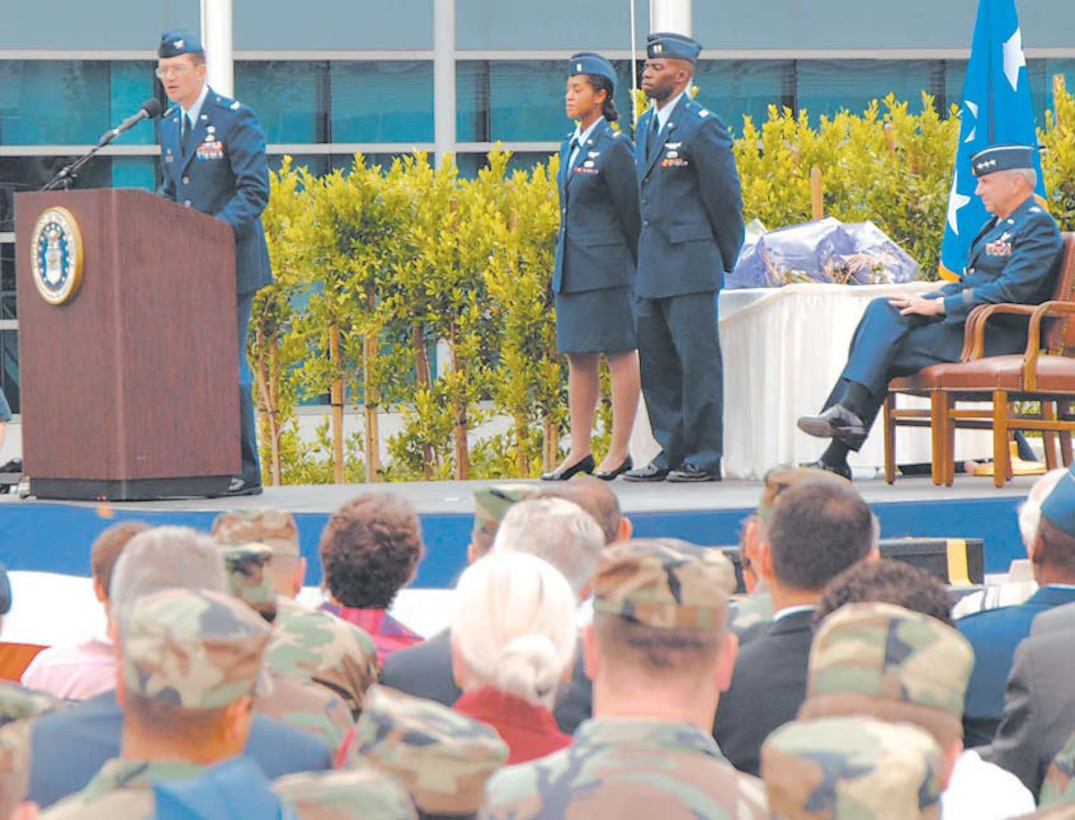 Col. Joe Schwarz, 61st Air Base Wing commander addresses the crowd during the SMC Wing standup. Lt. Gen. Michael Hamel, SMC commander (seated right), headed the historical ceremony at the Schriever Space Complex, July 31.