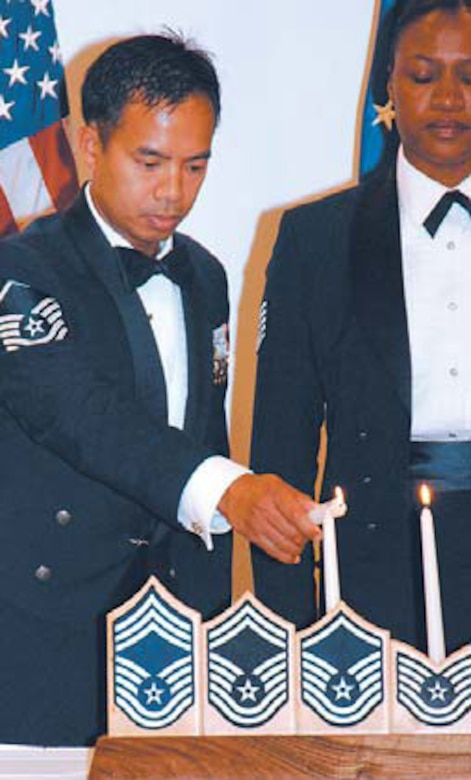Master Sgt. Narciso Abutin, lights the Candelabra representing the nine enlisted grades of the Air Force.