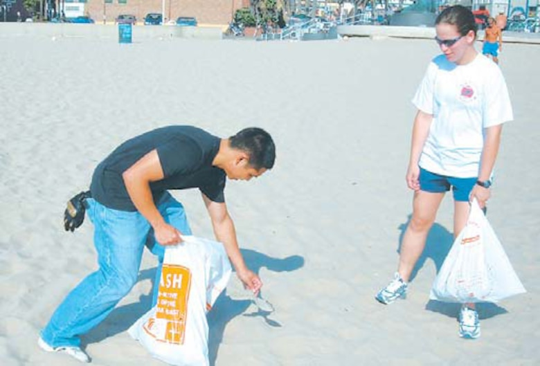 2nd Lt. Rey Jan Garma (left), Space Based Infrared Systems Wing, picks up trash from the sand as 2nd Lt. Margaret Goetz, Global Positioning Systems Wing, assists. They were both part of the SAS class which volunteered to clean the South Bay beaches.