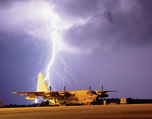 """Lightning strikes near an MC-130E Combat Talon on Duke Field's flight line. When """"lightning within five"""" is announced, wing members are instructed to seek immediate shelter. Personnel should also shut down their computers and unplug them unless they are protected by an uninterrupted power supply."""
