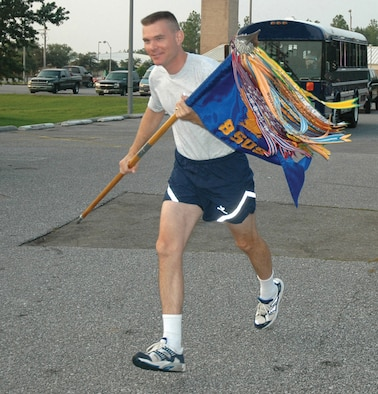 Lt. Col Paul Caltagirone, 8th Special Operations Squadron director of operations, takes his squadron guidon on its first leg of the return journey to its new home at Hurlburt Field Aug. 9. Squadron members took turns carrying the guidon through the 26-mile stretch.