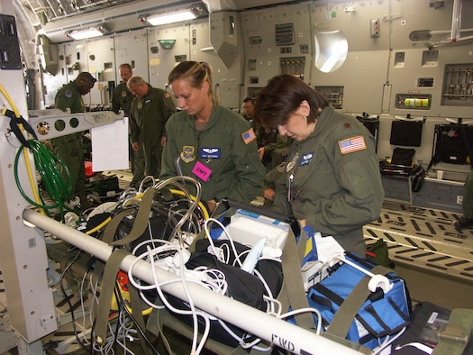 Two 932nd Aeromedical Evacuation Squadron members, Staff Sgt. Jennifer Higgins (left) and Maj. Shaun Carter, prepare their medical equipment before a training flight on board a visiting C-17 Globemaster from March Air Reserve Base, Calif.  Photo/Tech. Sgt. Gerald Sonnenberg