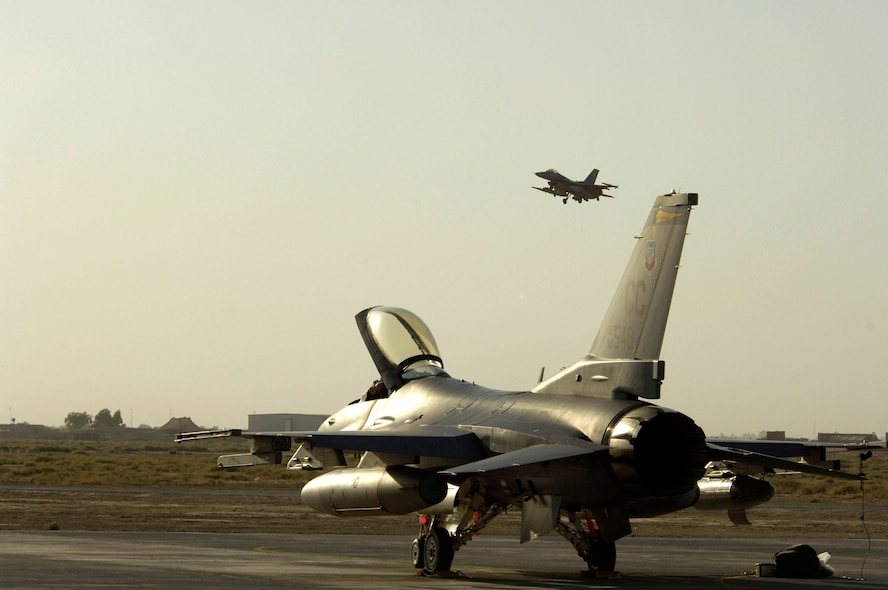 One F-16 Fighting Falcon taxis while another takes off from Balad Air Base, Iraq, Sept. 9. The F-16s, from Cannon Air Force Base, N.M., just arrived to support Operation Iraqi Freedom. (U.S. Air Force photo/Airman 1st Class Chad M. Kellum)